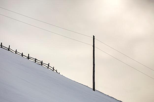 冬の風景。白い雪と明るい空のコピースペースに電流線と急な山の斜面。