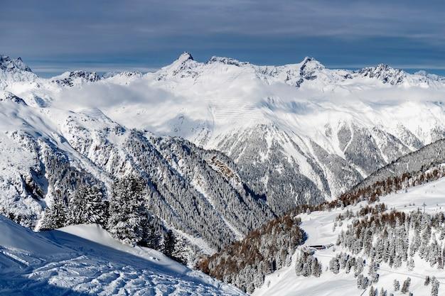 Зимний пейзаж; вид сверху горнолыжного курорта с голубым небом и морозными соснами, покрытыми снегом.