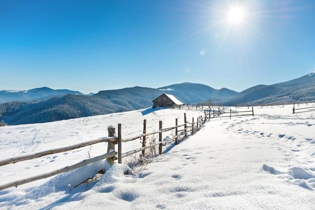 青い空と輝く太陽と白い雪の上の古い田舎の家と冬の風景