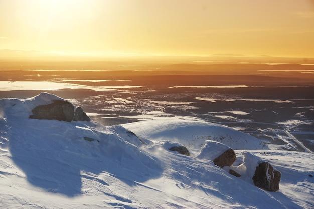 雪と風の強い天気の谷に小さな山と冬の風景