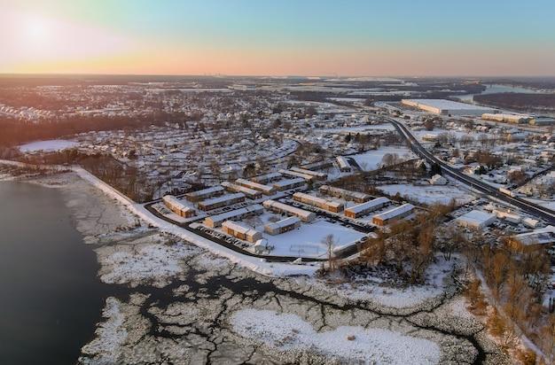 アメリカの住宅街で降雪後の冬の風景雪に覆われた家の近くに川が流れるアメリカの町