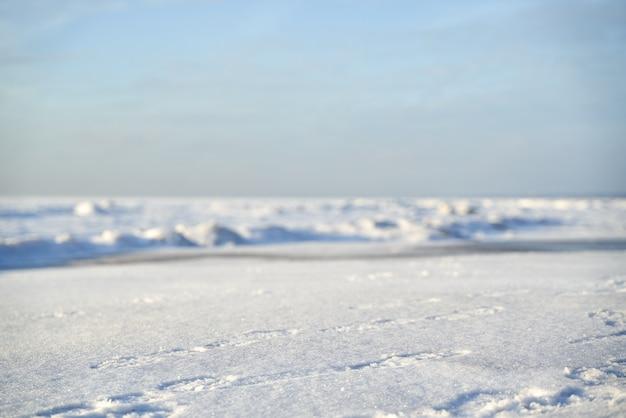 澄んだ空と湖の貯水池の氷の雪に覆われた冬の風景