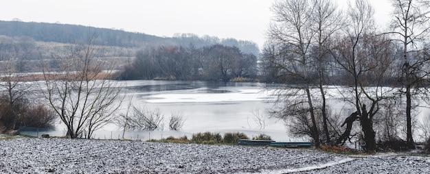 Зимний пейзаж с покрытой льдом и снегом рекой и деревьями у реки в пасмурный зимний день