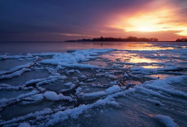 凍った湖と夕焼け空の冬の風景。自然の構成。