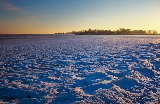 Зимний пейзаж с замороженным озером и закатным небом. композиция природы.