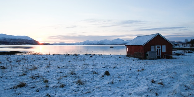 Зимний пейзаж с замерзшим озером и закатным небом с красным домиком для рыбака