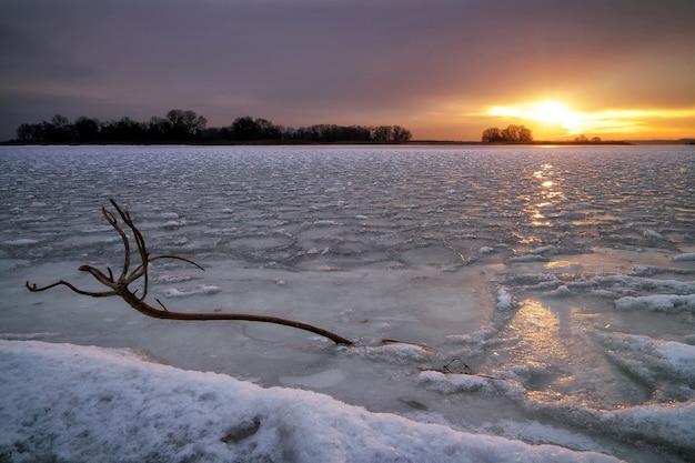 凍った湖、引っ掛かり、夕焼け空のある冬の風景