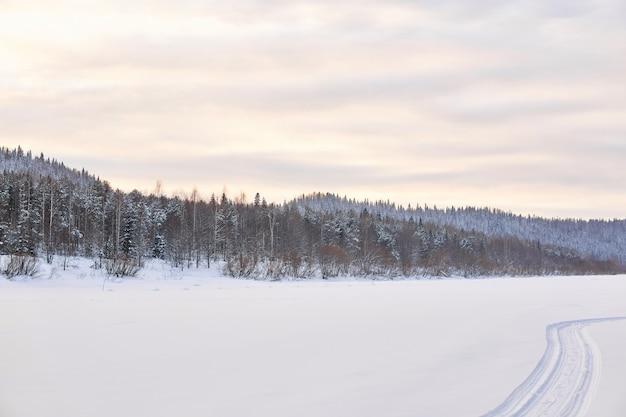 Зимний пейзаж с замерзшей рекой в заснеженной лесистой долине со следами снегохода в снегу