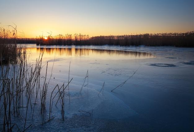Зимний пейзаж с замерзшей рекой, тростниками и закатным небом. рассвет