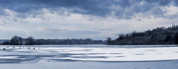 얼음과 눈 덮인 강과 그림 같은 흐린 하늘이 있는 겨울 풍경