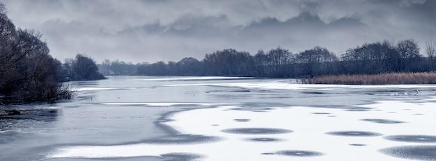 Зимний пейзаж с ледяным покровом и снегом у реки, драматическое облачное небо и деревья на берегу реки