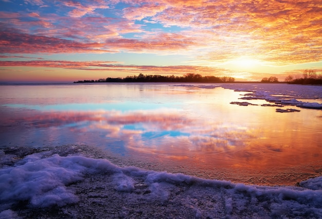 湖と夕日の燃えるような空と冬の風景。自然の構成。