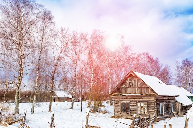 Winter landscape with old wooden house and trees with sunlight and blue cloudy sky. amazing winter scene