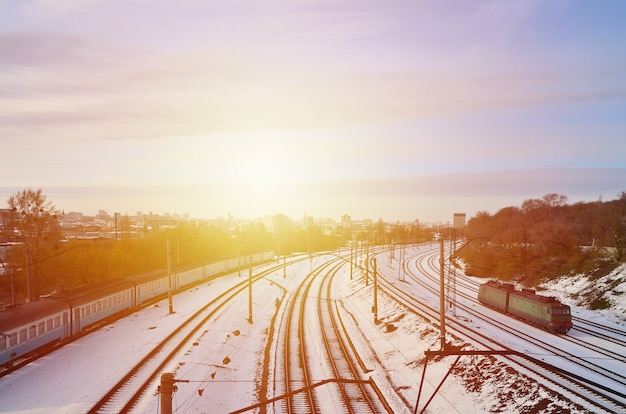 Winter landscape with a railway train against a cloudy sky background