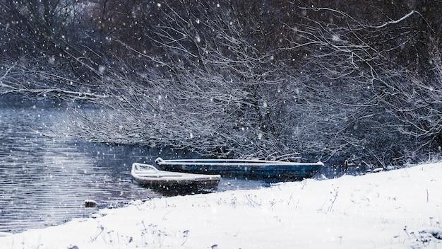Зимний пейзаж с рекой и лодками во время снегопада, река зимой