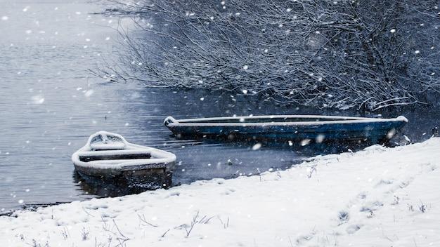 Зимний пейзаж с рекой и лодками во время снегопада
