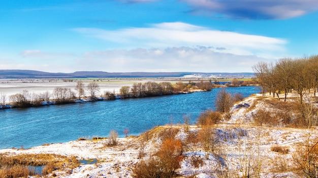 晴れた日に川と土手に木々と冬の風景