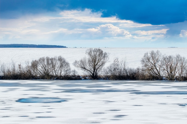 Winter landscape with river, trees, field and dramatic sky in sunny weather