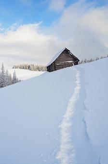 Зимний пейзаж с небольшим деревянным домиком в горах