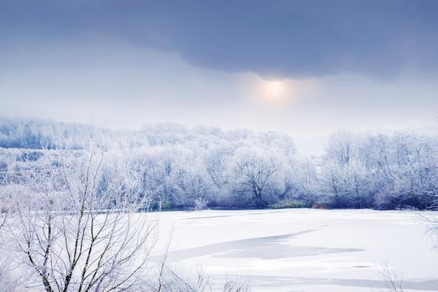 Зимний пейзаж с заснеженными деревьями у реки и небом с плотными облаками, сквозь которые светит солнце