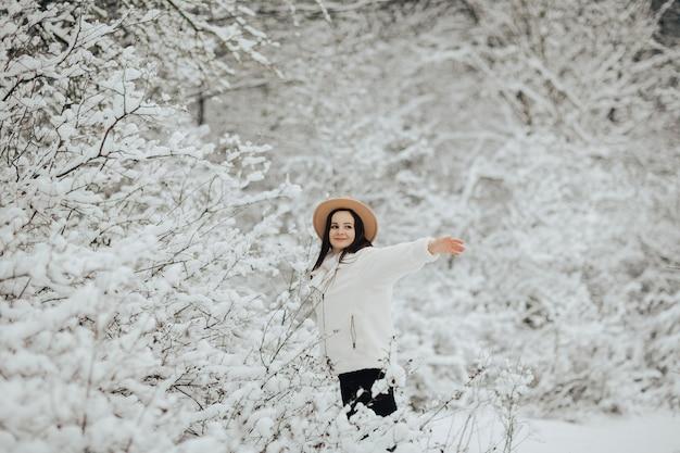 雪に覆われた木々と冬の風景。森の中の雪に覆われた木の近くに立っている幸せな女の子。
