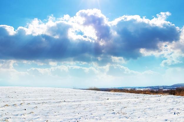 Зимний пейзаж со снежным полем и живописным небом с залитыми солнцем облаками