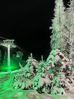 スキーリゾートのチェアリフトの背景に雪のトウヒの木と冬の風景