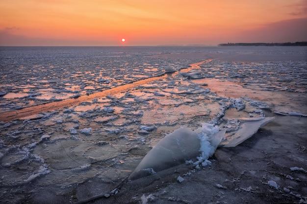 일몰 하늘과 얼어 붙은 강 겨울 풍경입니다. 새벽
