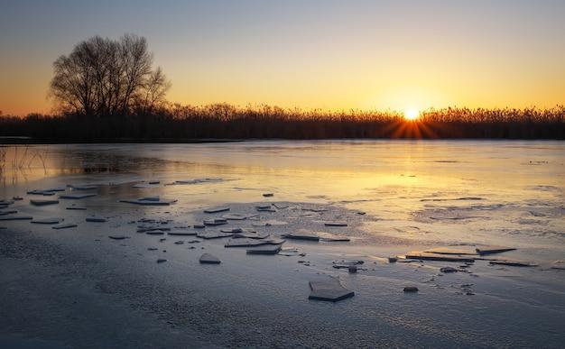 Зимний пейзаж с закатным небом и замерзшей рекой. рассвет