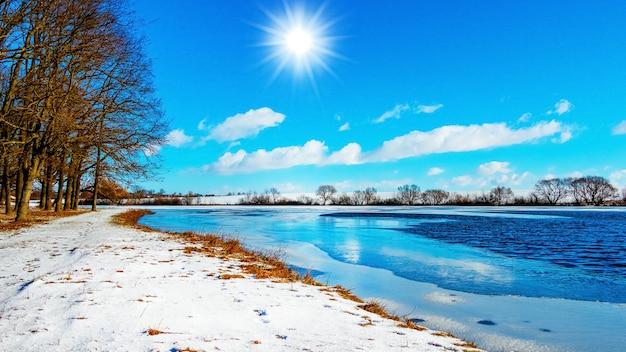 川と木々の上の青い空に太陽と冬の風景