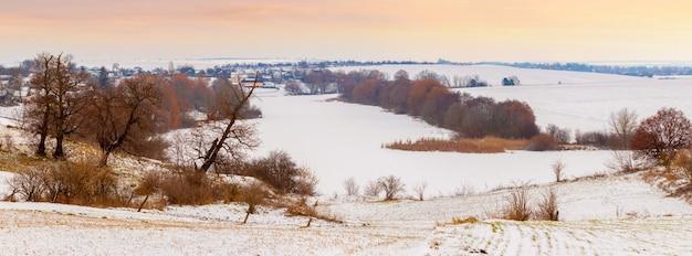 Зимний пейзаж с деревьями возле реки, покрытой льдом и снегом, утром во время восхода солнца