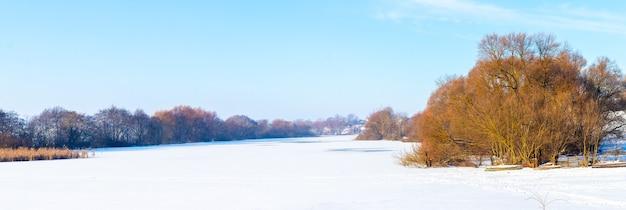 晴れた日、パノラマ、氷と雪で覆われた川のほとりに木がある冬の風景