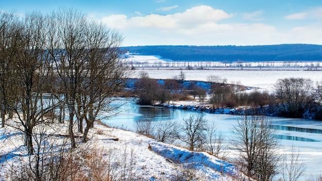 Зимний пейзаж с деревьями на высоком берегу реки в солнечный день