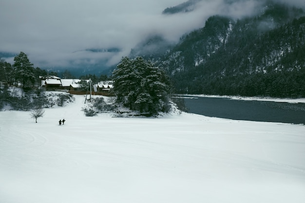 Winter landscape with a village in the mountains on the bank of a mountain river