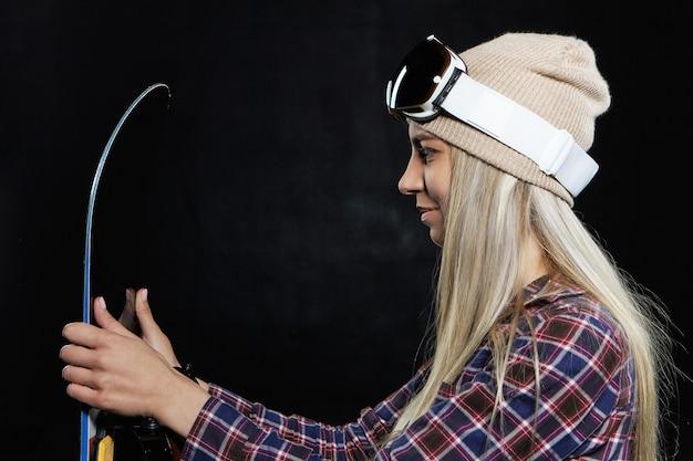 冬のレジャー、エクストリームスポーツとアクティビティのコンセプト。帽子とスキーマスクを身に着けている幸せな若いブロンドの女の子のスノーボーダーのプロフィールの肖像画は、黒いスノーボードで屋内でポーズをとって、乗車のために服を着る