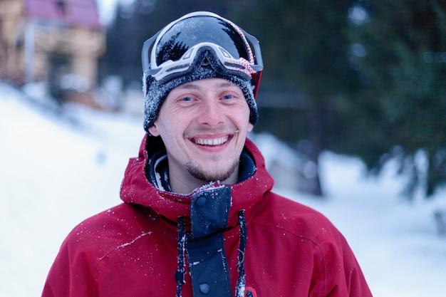 Зима, отдых, спорт и люди концепции - человек, катающийся на сноуборде в горах. сноубордист отдыхает на вершине горы на фоне голубого неба. лыжный курорт.