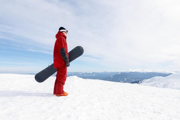 겨울, 레저, 스포츠, 사람 개념 - 스노보더는 오지 슬로프에 서서 스노보드를 들고 있습니다. 스키 컨셉