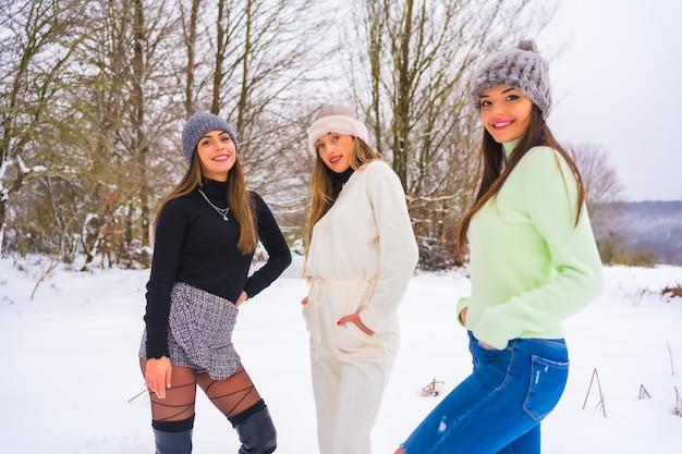冬のライフスタイル、雪に覆われた松の木の横で雪を楽しんでいる冬の服とウールの帽子を持つ白人の女性の友人、自然の中での休日