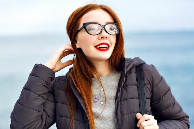 海辺で歩いているかなり流行に敏感な生姜女性の冬のライフスタイルの肖像画、合計黒のスタイリッシュな服、寒い雨の日、バックパック、革のブーツ、孤独。