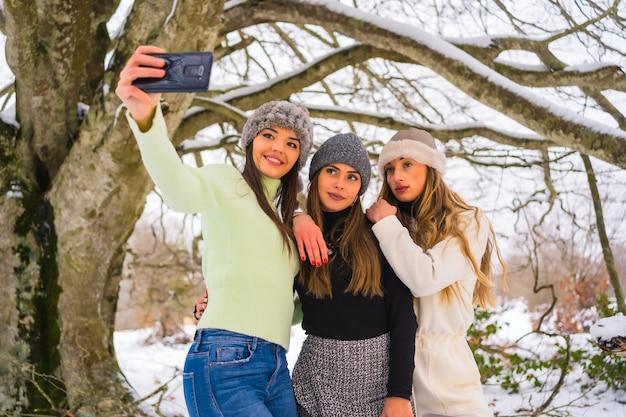 冬のライフスタイル、木の下の雪の中で携帯電話で自分撮りをしている3人の美しい白人の友人、自然の中での休日