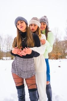 冬のライフスタイル、冬の服装と雪の中で抱き締めるウールの帽子を持つ3人の美しい白人の友人、自然の中での休日