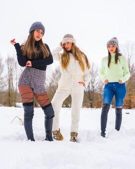 冬のライフスタイル、冬の服装と雪を楽しむウールの帽子を持つ3人の白人のガールフレンド、自然の中での休日