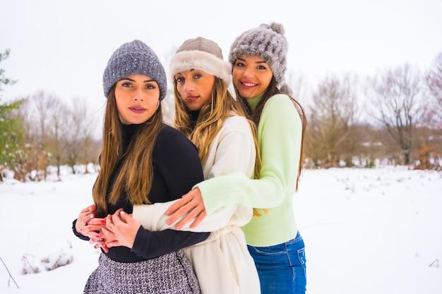 冬のライフスタイル、雪の中で抱き締める3人のかわいい白人のガールフレンド、自然の中での休日