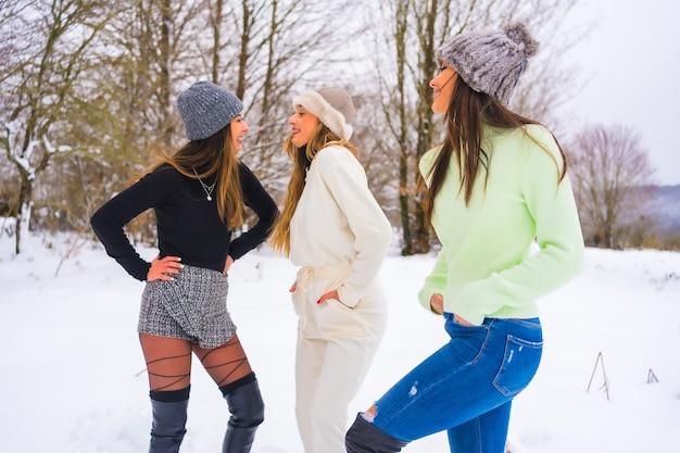 冬のライフスタイル、冬の服装と雪に覆われた松の木の横で雪を楽しんでいるウールの帽子を持つ若い白人の友人、自然の中での休日