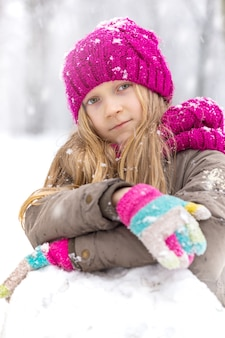 Winter - little happy smiling girl outdoors at the snowfall time