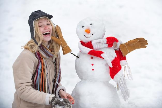 Концепция зимней любви. делаем снеговика и зимние забавы. подмигните. зимний портрет молодой женщины