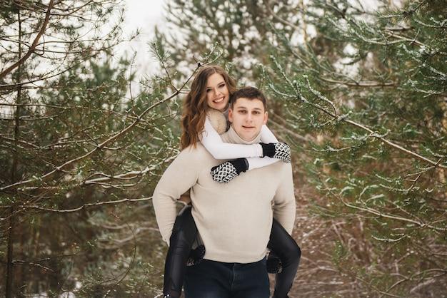 氷上の冬のラブストーリー。冬の森でスタイリッシュな恋人の男の子と女の子。