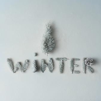 雪の壁にクリスマスツリーをあしらった木の枝と松ぼっくりでできた「冬」。シーズンコンセプト。フラットレイ。
