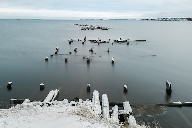 Winter minimalistic evening landscape with an old ruined pier in the white sea.