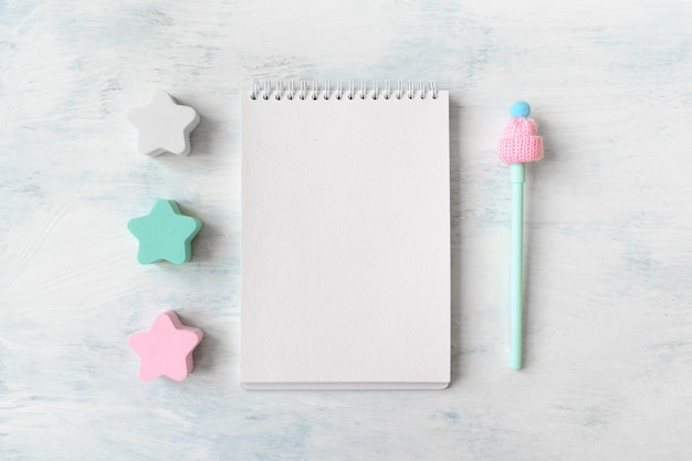 Winter mockup with open white three pastel blue and pink star, notebook and pen